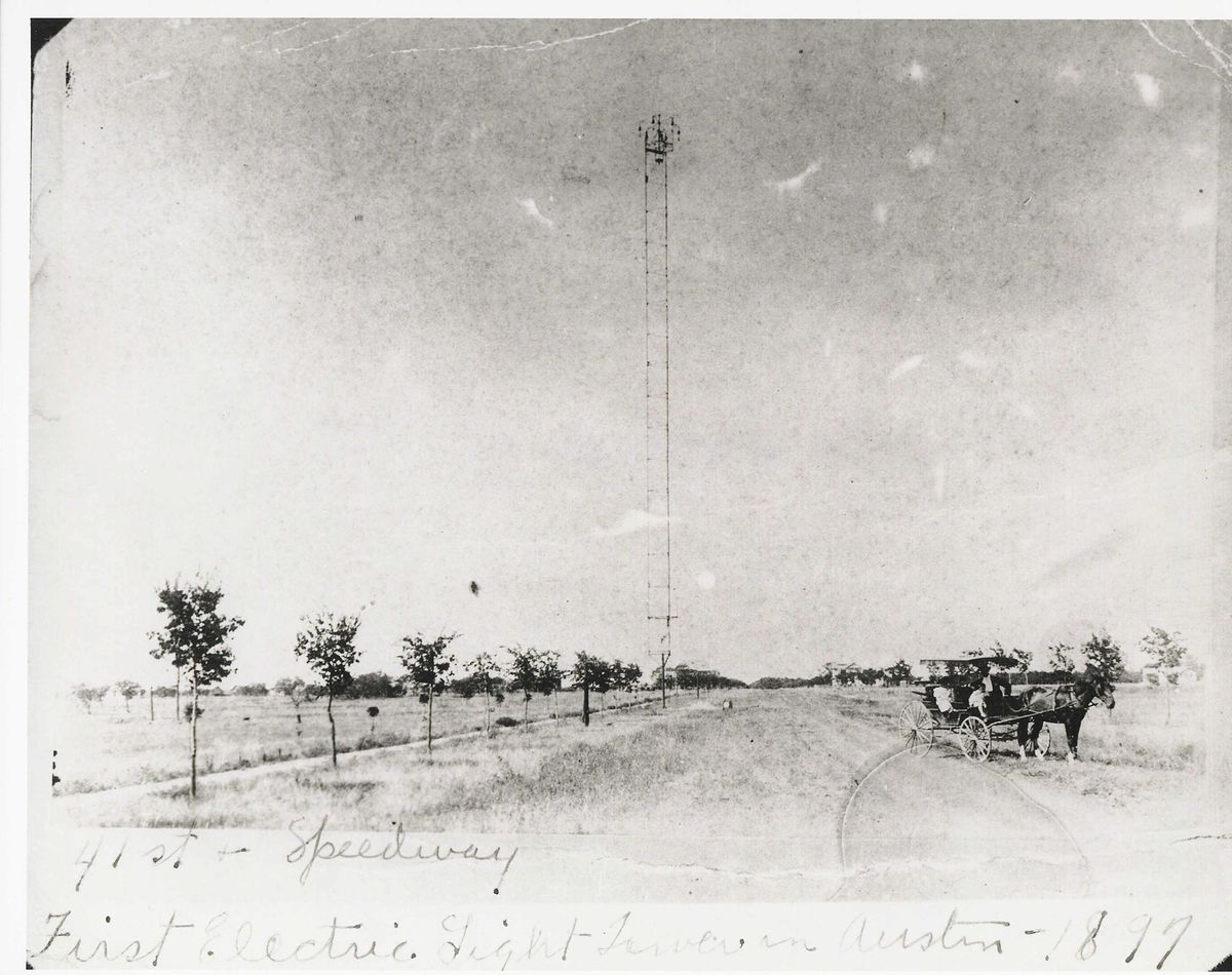 Old black and white photo of moonlight tower surrounded by a field bordered by a small line of trees and a road, horse-drawn wagon