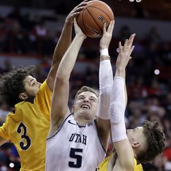 Utah State's Sam Merrill (5) shoots as Wyoming's Kwane Marble II (3) and Jake Hendricks defend during the first half of an NCAA college basketball game in the Mountain West Conference men's tournament Friday, March 6, 2020, in Las Vegas.