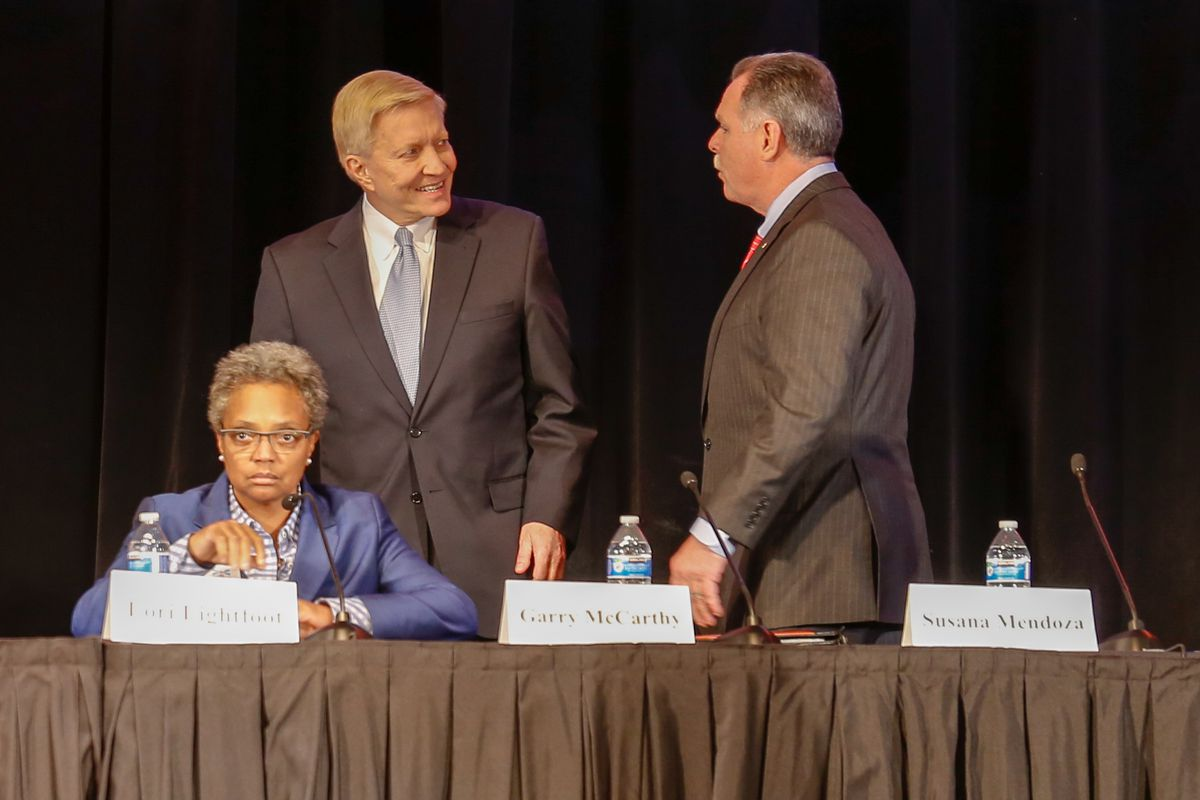 Mayoral candidates Bob Fioretti and Garry McCarthy chat behind Lori Lightfoot ahead of a forum Thursday evening at Steinmetz College Prep on the Northwest Side. | Nader Issa/Sun-Times