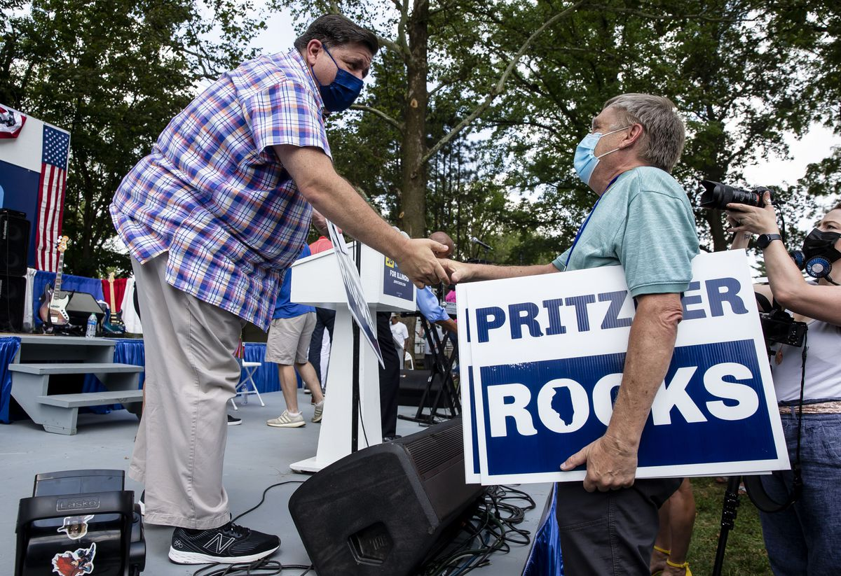 """Illinois Gov. J.B. Pritzker gets a """"Pritzer Rocks"""" sign from Peter Janko, Democratic state central committeeman for 14th Congressional District of Illinois, during Governor's Day at the Illinois State Fair in Springfield on Wednesday."""
