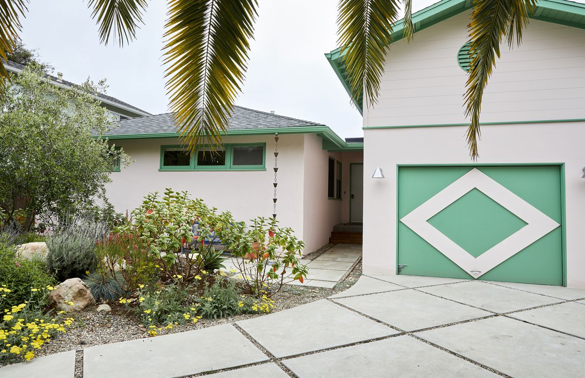 The exterior of a house painted white and green. In the foreground are the branches of a palm tree and flowering shrubbery.