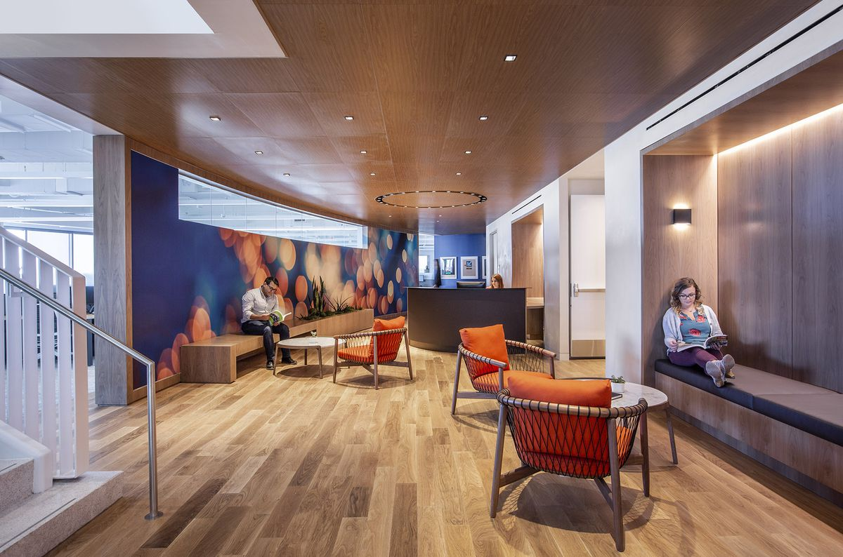 Lobby area with wood floor and ceilings modern receptionist desk, receptionist, blue wall with graphic mural recessed lighting white man and white women reading on different benches
