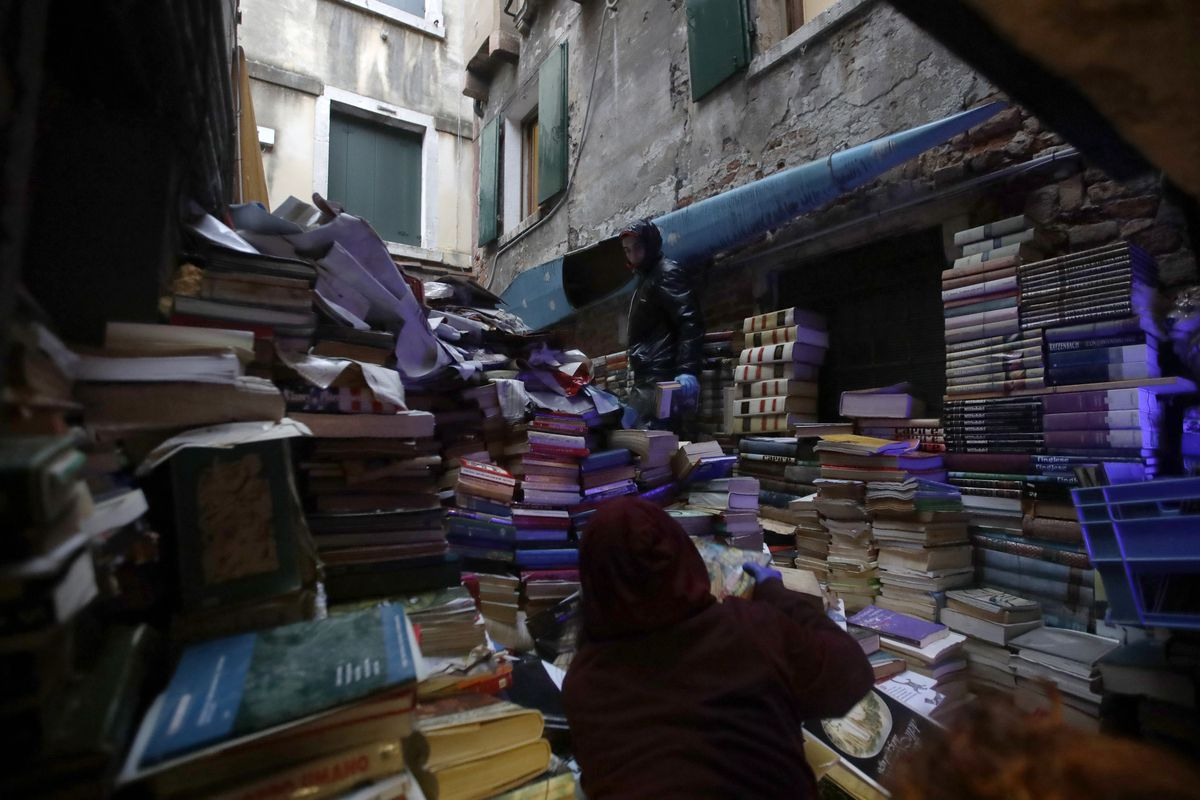 """Volunteers pile up damaged books from renowned bookstore """"Acqua Alta"""" (High Water) after flooding in Venice, Italy. Exceptionally high tidal waters returned to Venice on Friday, prompting the mayor to close the iconic St. Mark's Square."""