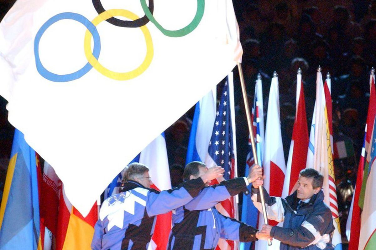 FILE - Salt Lake Mayor Rocky Anderson waves the Olympic flag before handing it off to IOC President Dr. Jacques Rogge and Torino Mayor Sergio Chiamparino during closing Salt Lake 2002 Winter Olympic Games Closing ceremonies Sunday, Feb. 24, 2002 at the Ri