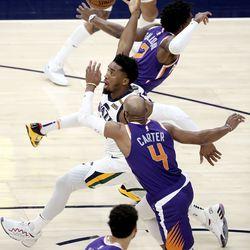Utah Jazz guard Donovan Mitchell (45) dribbles between Phoenix Suns guard Langston Galloway (2) and Phoenix Suns guard Jevon Carter (4) during a preseason NBA game at the Vivint Smart Home Arena in Salt Lake City on Monday, Dec. 14, 2020. The Jazz beat the Suns 111-92.