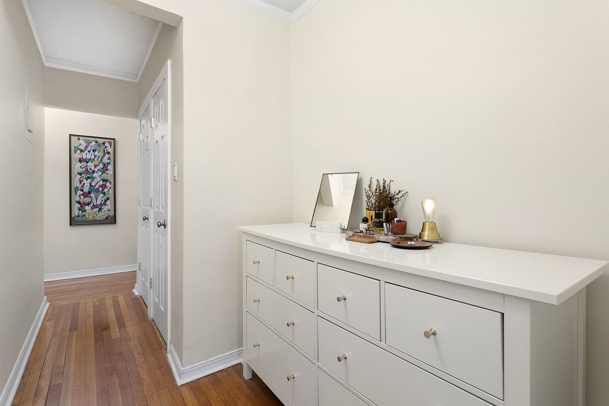 A hallway with beige walls, hardwood floors, and a beige cabinet.