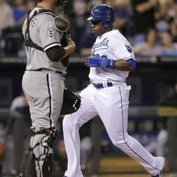 Kansas City Royals' Jason Bourgeois runs past Chicago White Sox catcher Tyler Flowers to score on a sacrifice fly by Billy Butler during the third inning of a baseball game Wednesday, Sept. 19, 2012, in Kansas City, Mo.