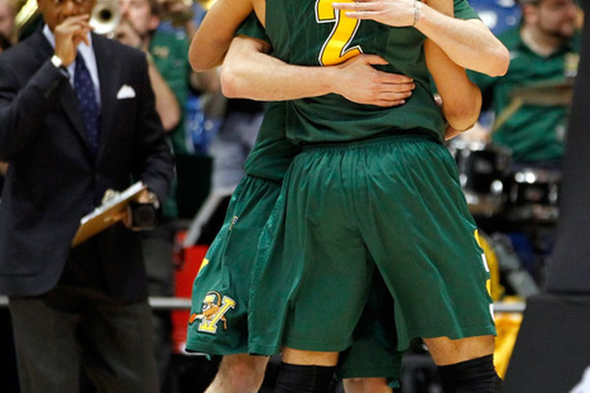 Matt Glass #34 and Luke Apfeld #2 of the Vermont Catamounts celebrate after they won 71-59 against the Lamar Cardinals.