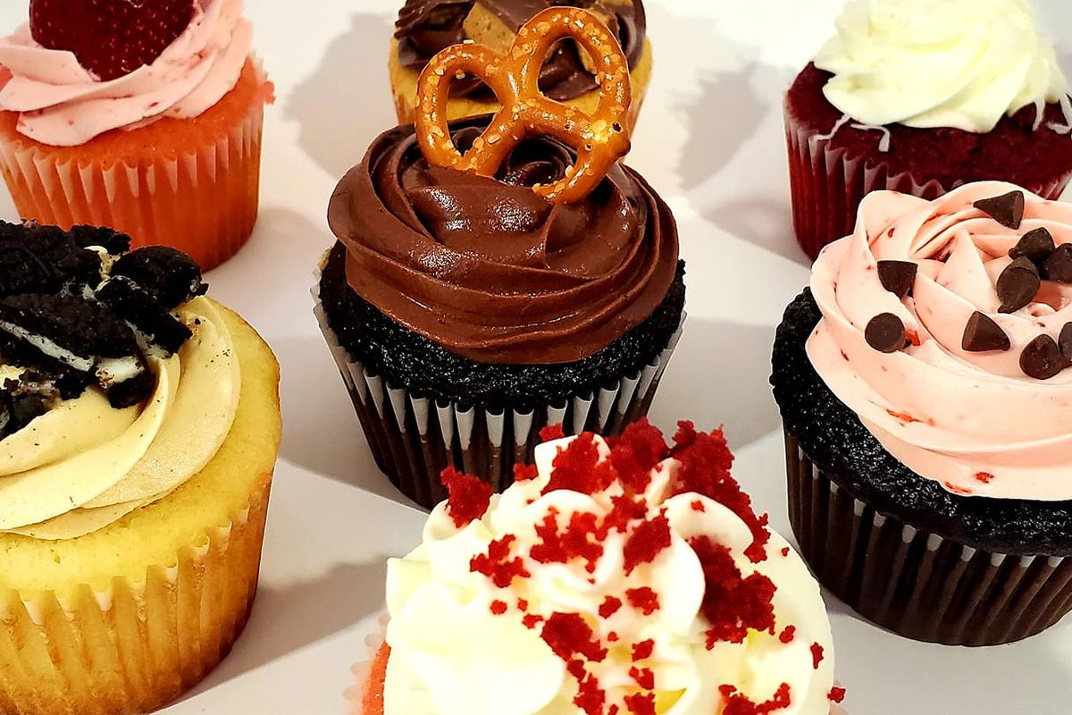 Six colorful cupcakes including red velvet, chocolate, vanilla, and strawberry topped with pink, chocolate, and vanilla frosting