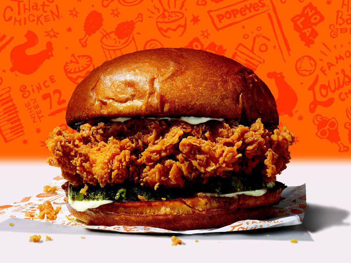 Popeyes fried chicken sandwich on a bright orange background