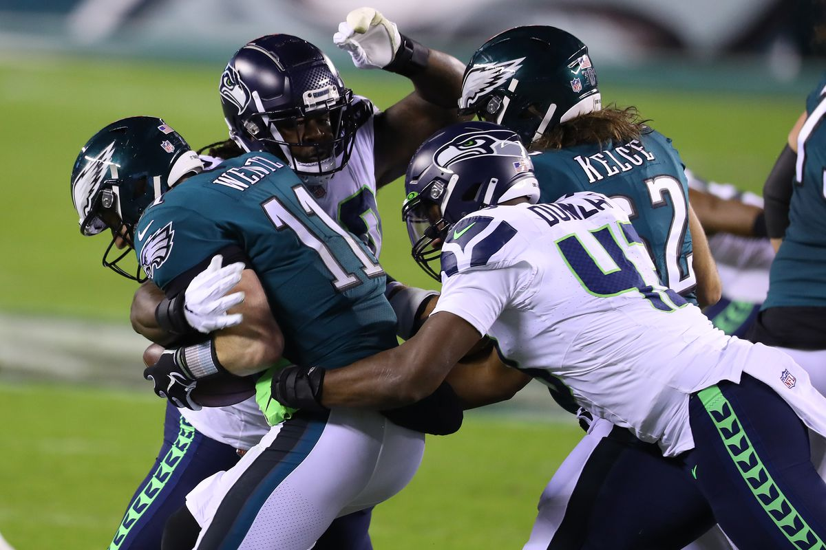 Jarran Reed #90 and Carlos Dunlap #43 of the Seattle Seahawks sack Carson Wentz #11 of the Philadelphia Eagles during the second quarter at Lincoln Financial Field on November 30, 2020 in Philadelphia, Pennsylvania.