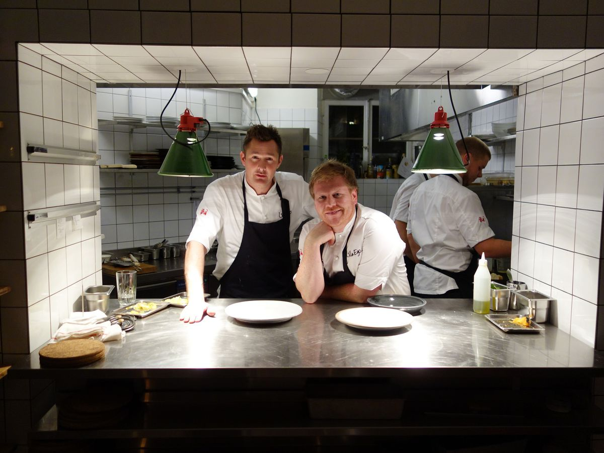 Two chefs, Tom Sjöstedt and Daniel Räms, stand looking out from a restaurant kitchen