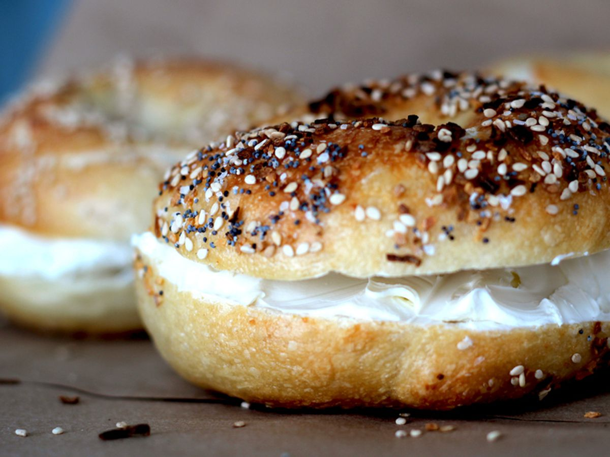 Crusty poppyseed topped bagel, sliced with a thick layer of cream cheese in the middle
