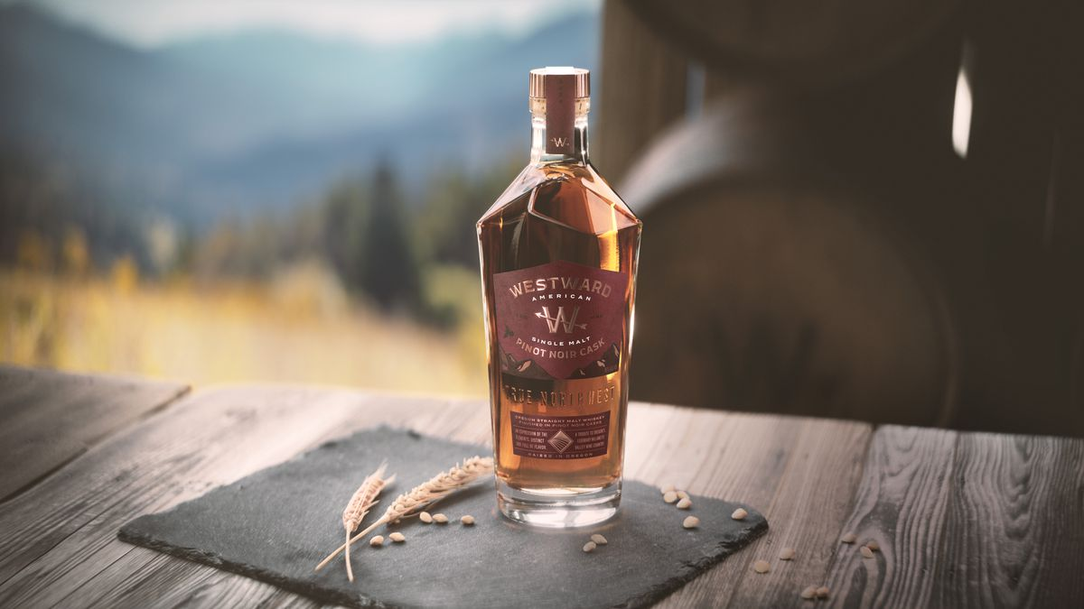 a bottle of whiskey sits on a wine barrel with mountains in the background