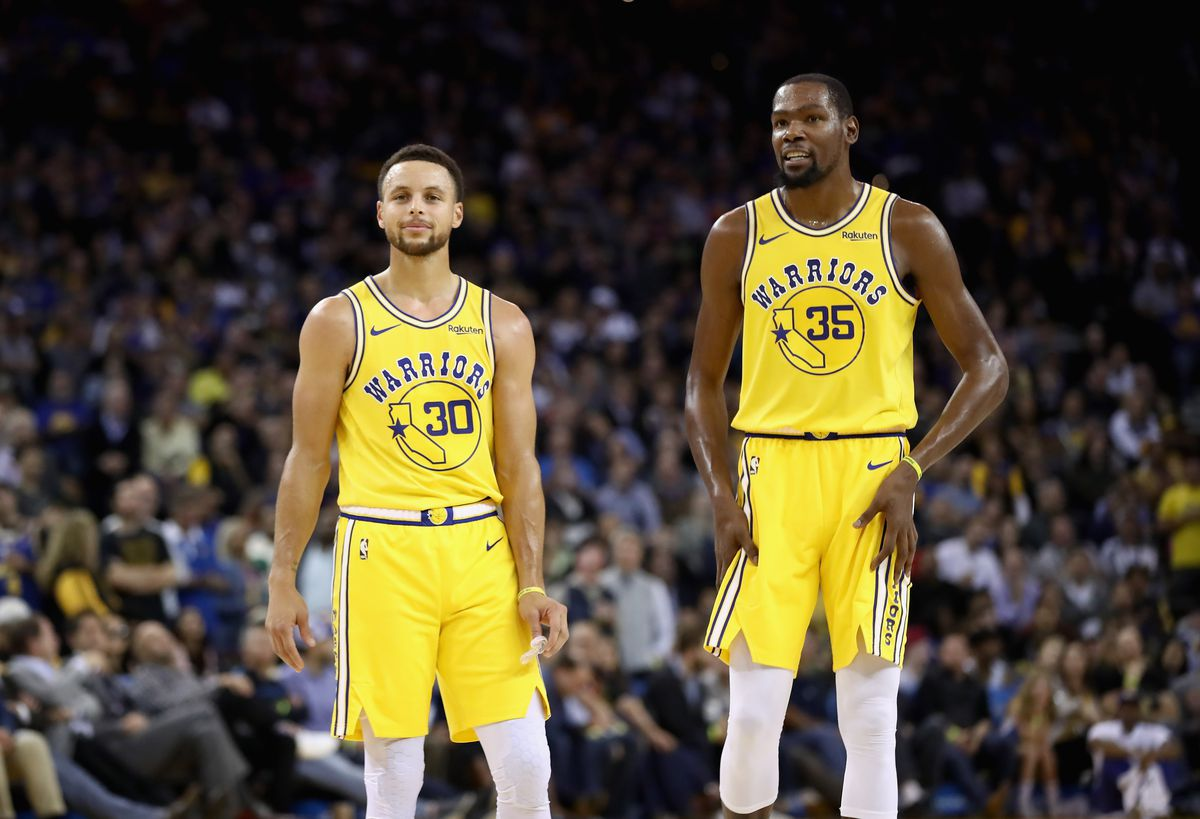 Stephen Curry and Kevin Durant stand next to each other in yellow Warriors jerseys
