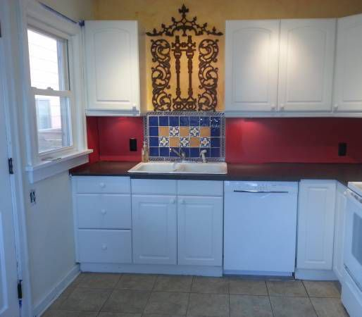 A kitchen with a blue and gold backsplash and red and gold walls