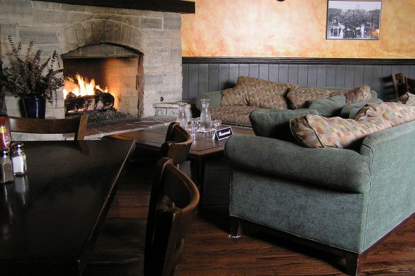 A fireplace surrounded by comfy couches.