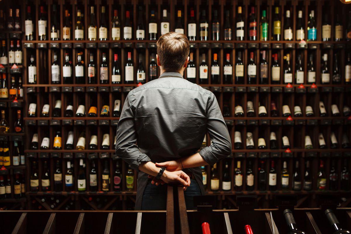 A bartender stands in a wine cellar