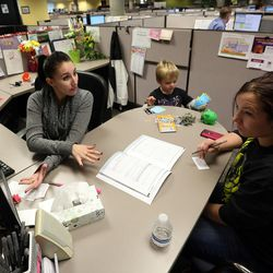 Emplyoment counselor Sarah Guzman talks with Audra Eagle about her plan to find employment as Eagle's son, Brody, plays with toys with at the Utah State Metro Employment Center in Salt Lake City on Friday, Dec. 11, 2015.