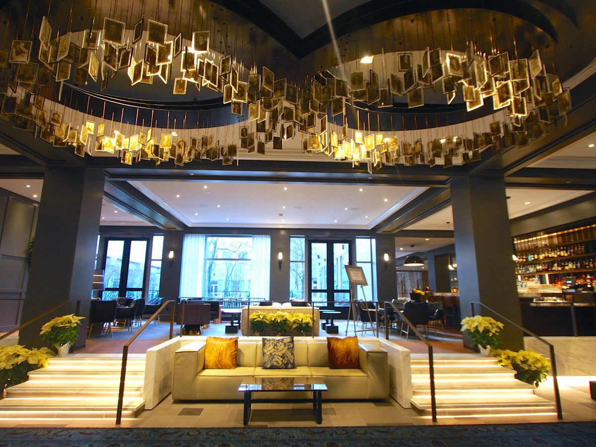 The interior of the lobby at the Logan Philadelphia. There is a couch, large chandeliers, and stairs leading to a landing with floor to ceiling windows.