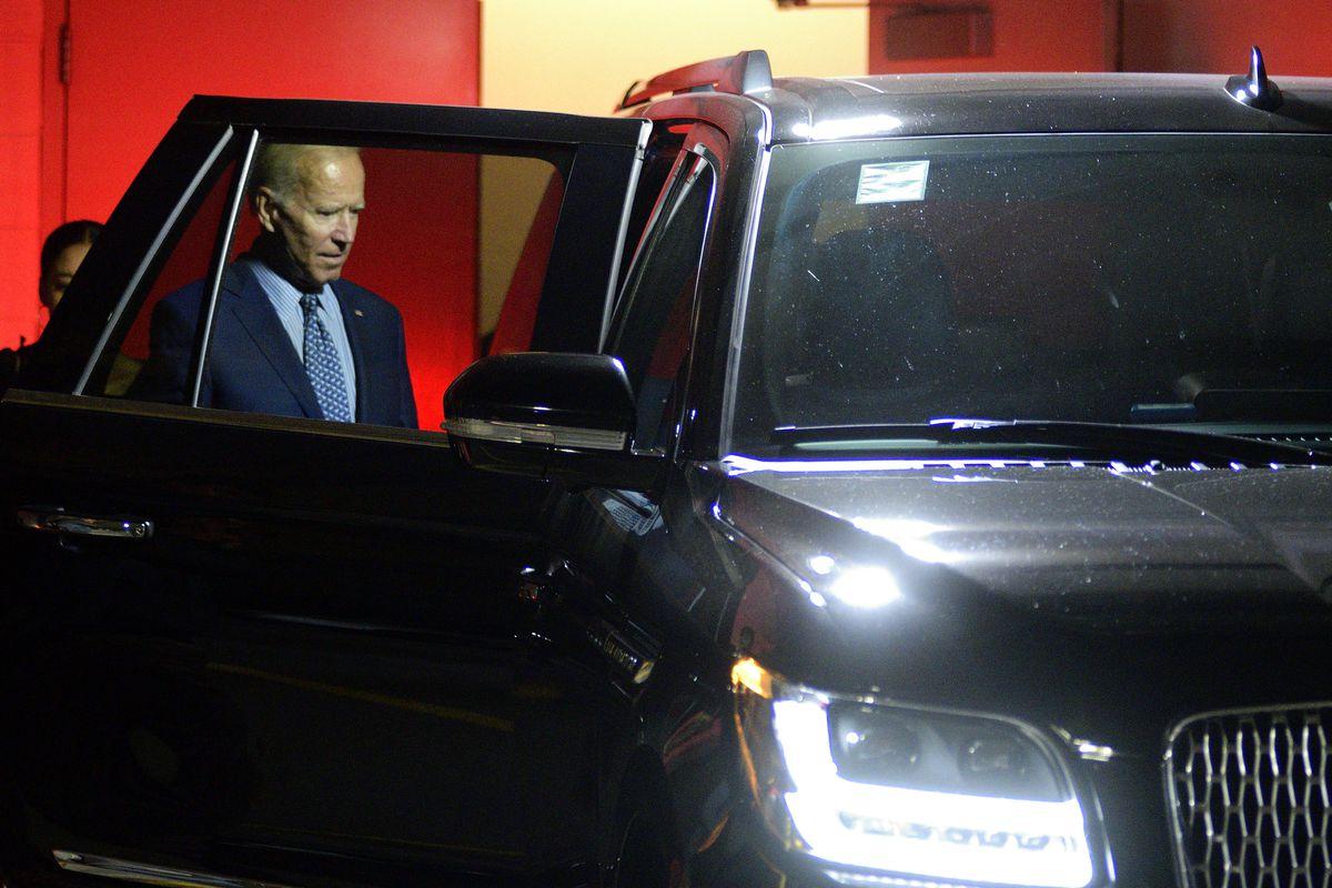 Joe Biden getting into a large black car.