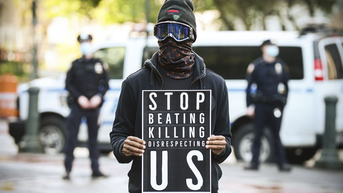 """A protester dressed all in black, with a scarf around their face and ski goggles over their eyes holds a black sign with white letters that read: """"Stop beating killing disrespecting US."""""""