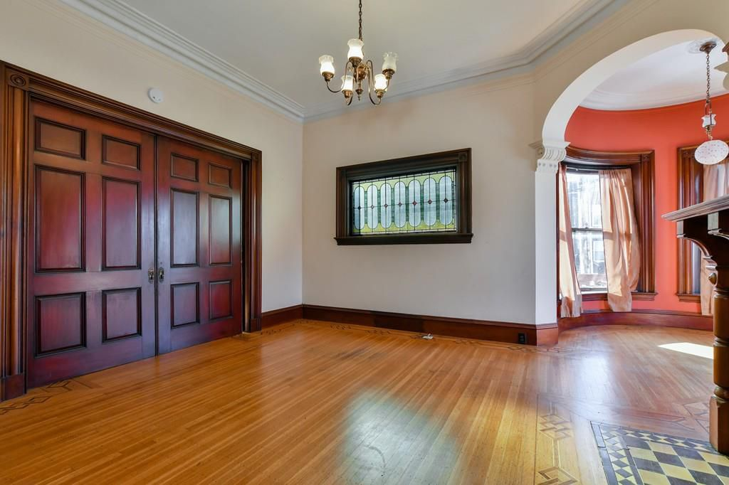An empty living room area with two closed sliding doors and a stained glass window.