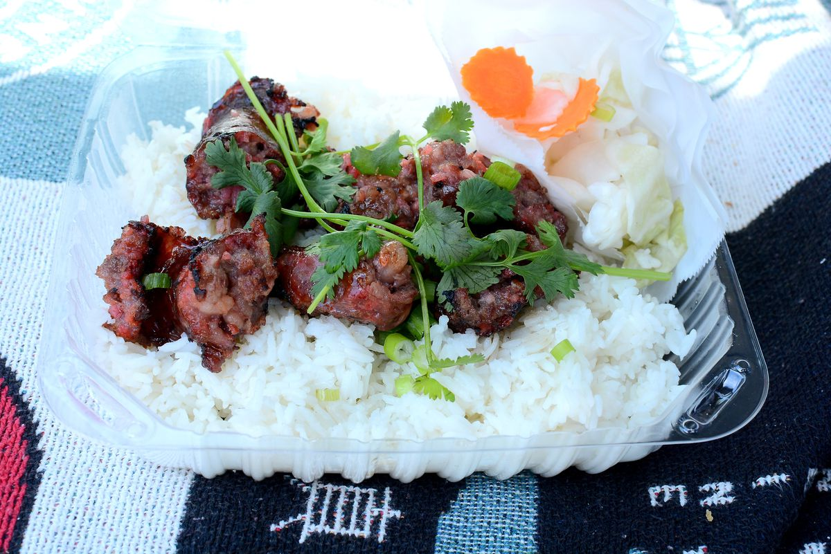 A plastic container full of steamed rice and sausage.