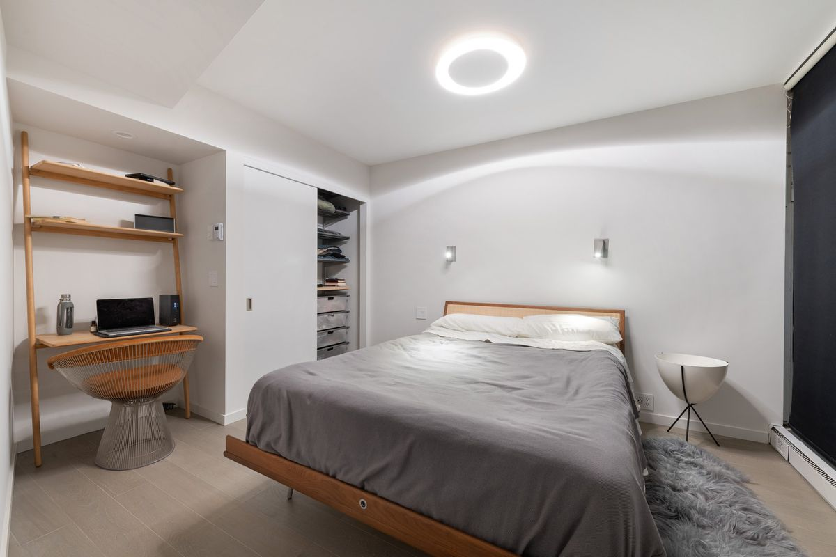 A wood-frame bed with a gray comforted against a wall next to the closet and desk with a chair.