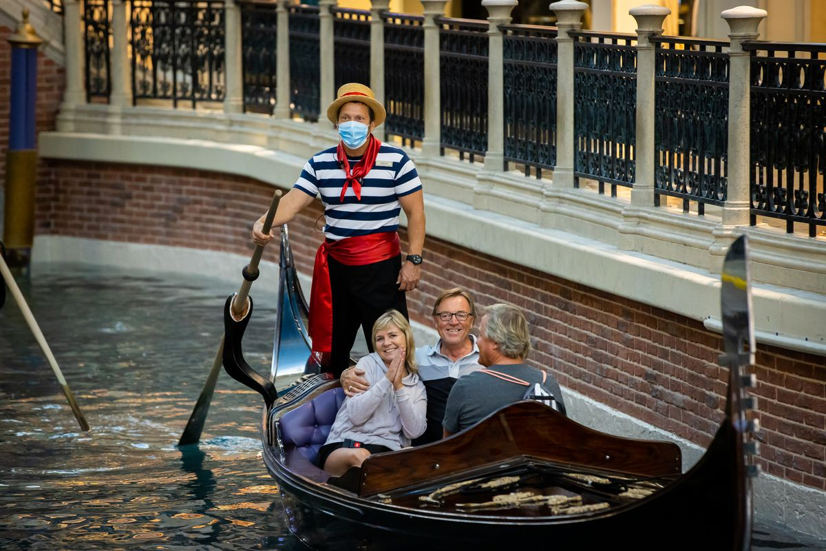 A gondolier wears a mask while customers do not at the Venetian.