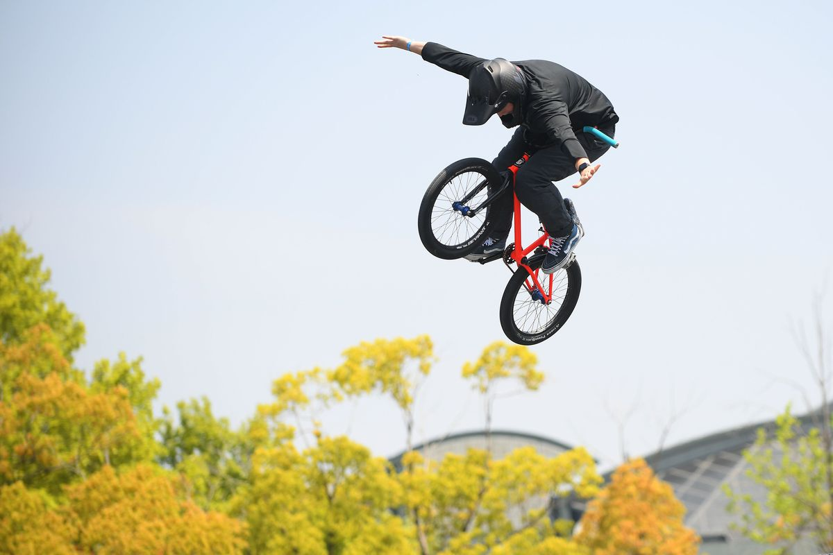 Hannah Roberts airborne at the 2019 World Cup for BMX, atop her bike, arms splayed out and head down. She is wearing a black helmet and jacket.