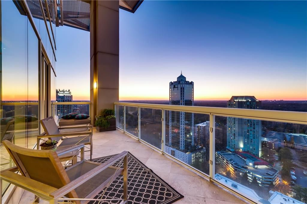 A huge balcony with chairs at sunset.