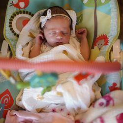 Aria Newbold, 3 weeks old, sleeps while her family eats dinner at their home in Kaysville on Tuesday, April 7, 2020.