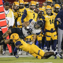 Utah State running back Jaylen Warren (20) fumbles the ball as Kent State cornerback Keith Sherald Jr. (5) makes the tackle during the first half of the Frisco Bowl NCAA college football game Friday, Dec. 20, 2019, in Frisco, Texas. Kent State linebacker Mandela Lawrence-Burke recovered the ball.