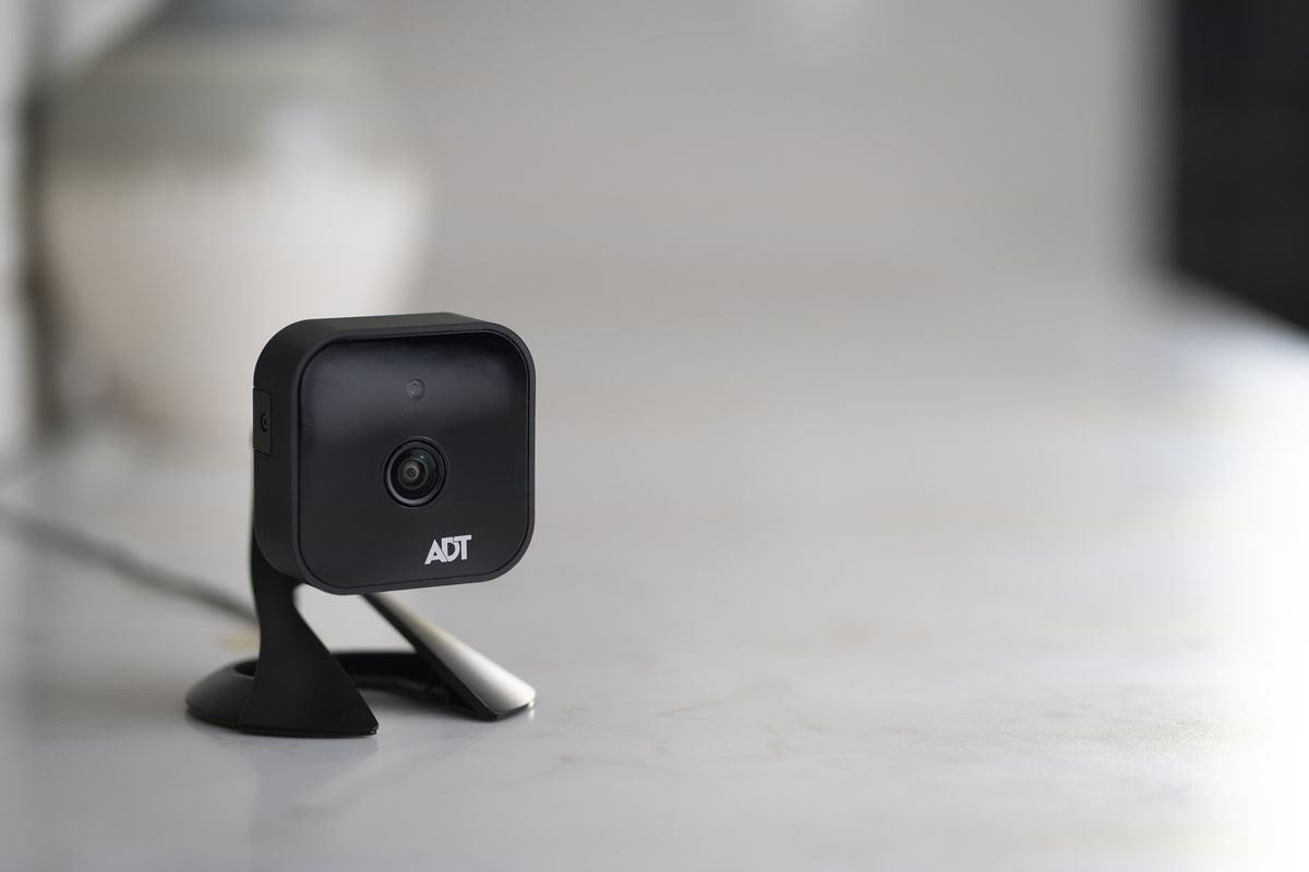 An ADT security camera sits on a grey countertop in a home.