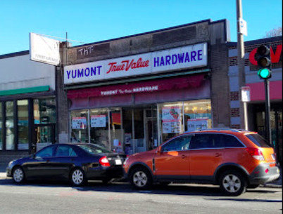Exterior of a hardware store on a city street with cars parked in front.