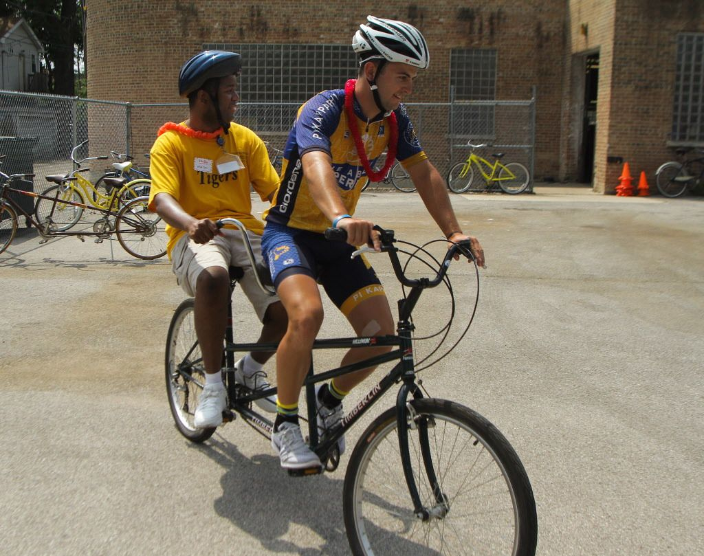 Daniel Gramer, from the Ability Experience, shares a tandem with Marcus Womack, of Envision Unlimited, on Wednesday at a partyat the Envision Unlimited Westtown Center.   Leslie Adkins/For the Sun-Times