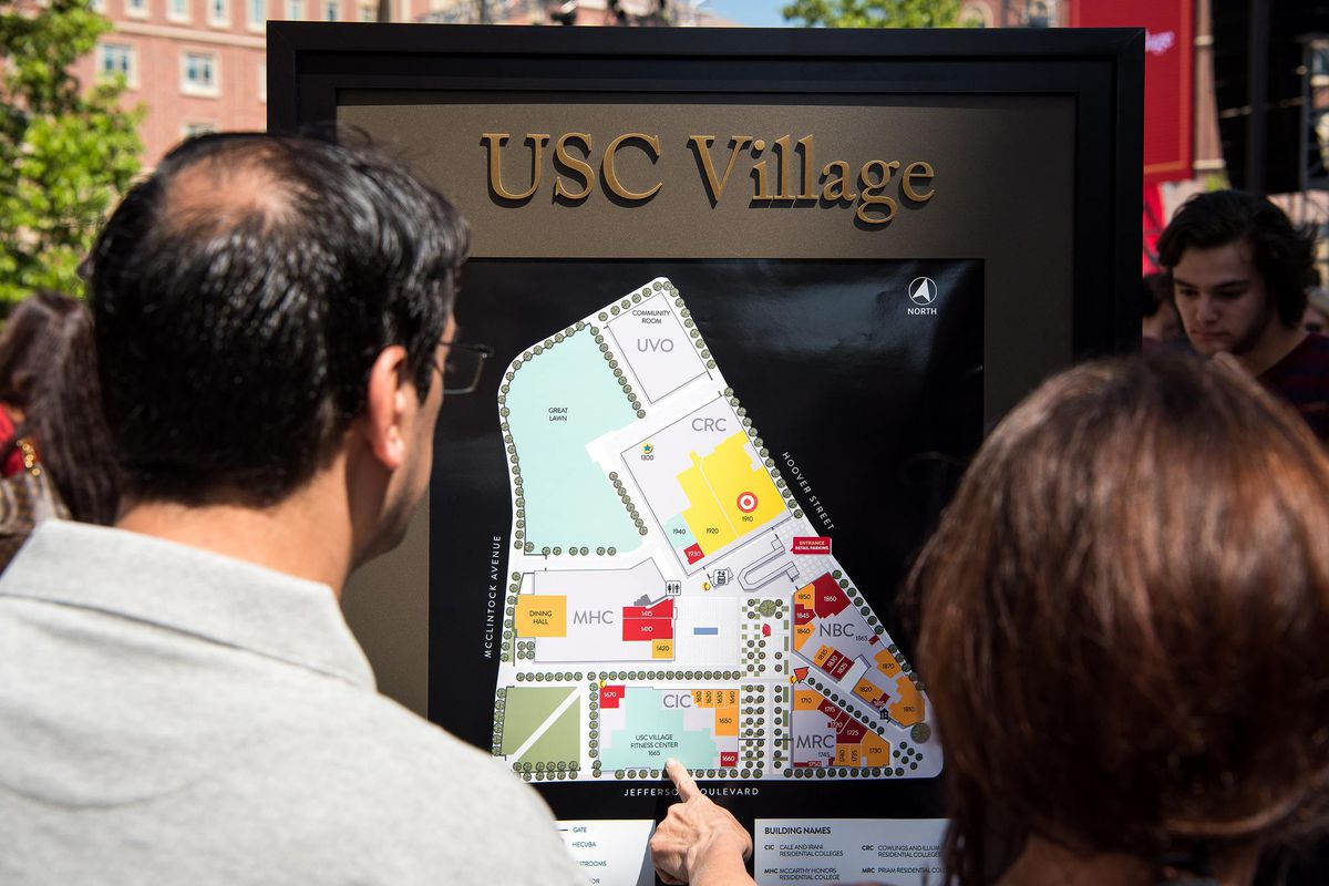 Onlookers point at a map at USC Village.