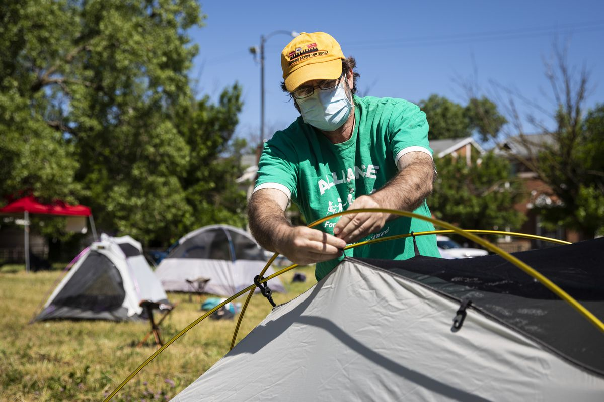 """Fran Tobin, 59, of Rogers Park, volunteers with the Obama Center CBA Coalition and helps erect a """"tent city"""" on a vacant lot at East 63rd Street and South Blackstone Avenue to call for more affordable housing in Woodlawn, Thursday morning, June 11, 2020."""