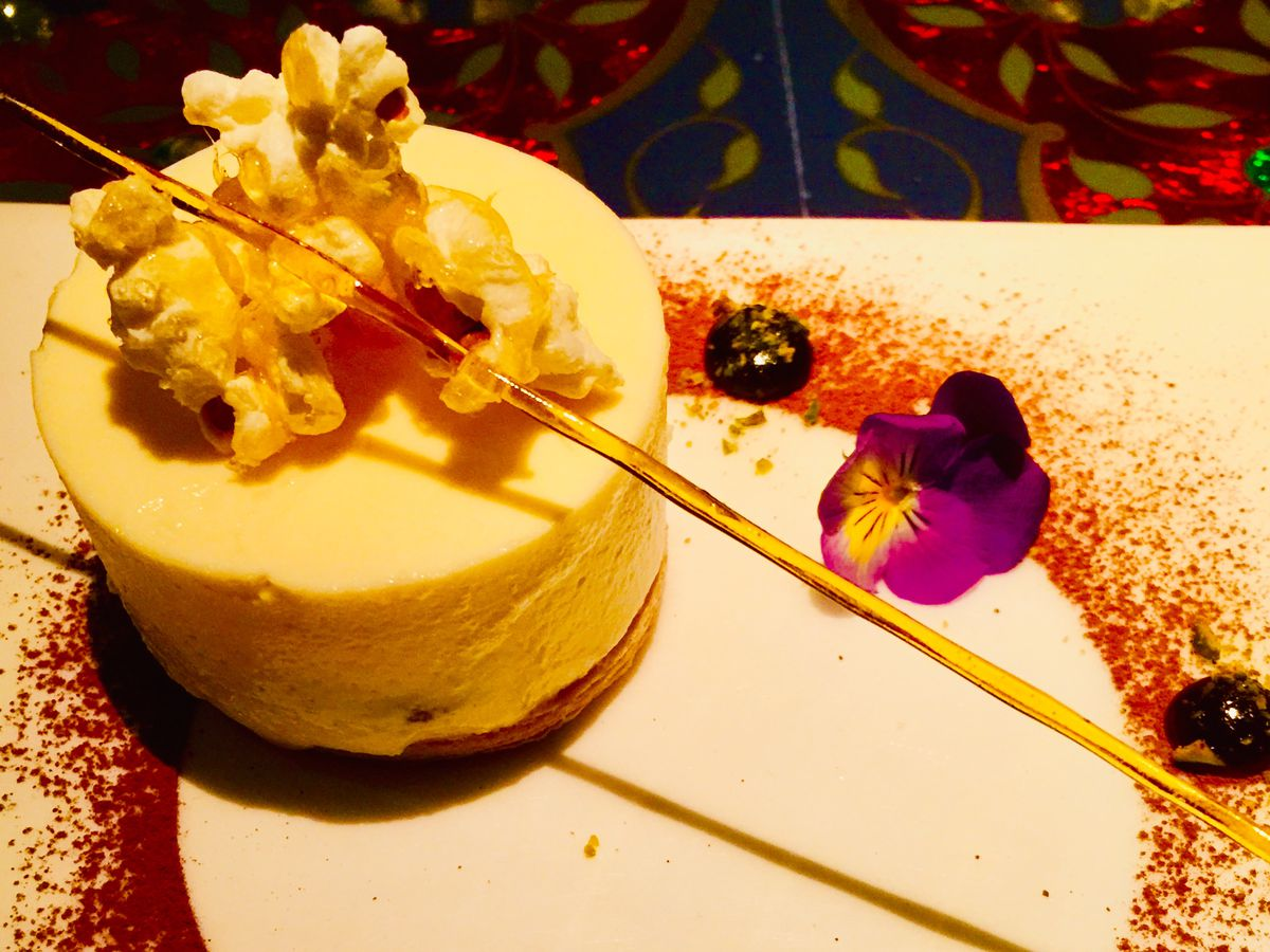 An elaborate dessert on a plate dusted with cocoa powder and fruit at Amaya in Belgravia