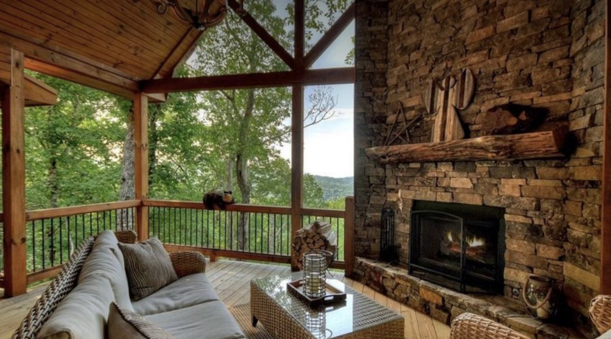 Covered porch with stacked stone fireplace, couch, chair, table, and views of the mountains.