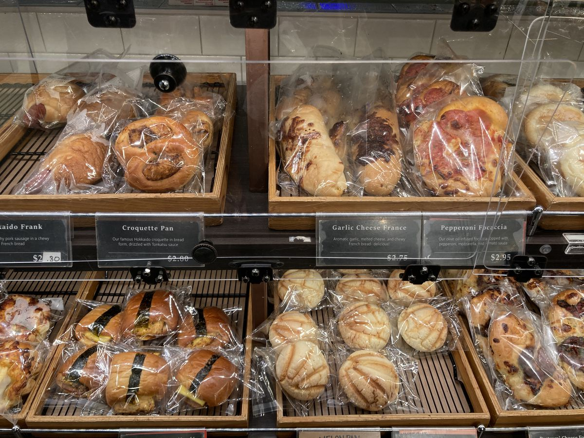 A pastry case with wooden boxes containing various muffins, cookies, and sweets wrapped individually in celophane