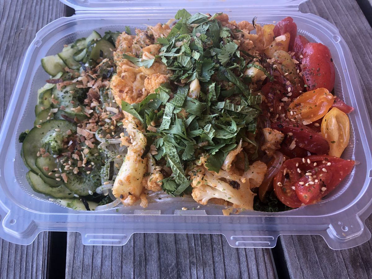 A takeout container is filled with red-hued cauliflower, sliced grape tomatoes, and cucumbers covered in furikake at Meals 4 Heels.