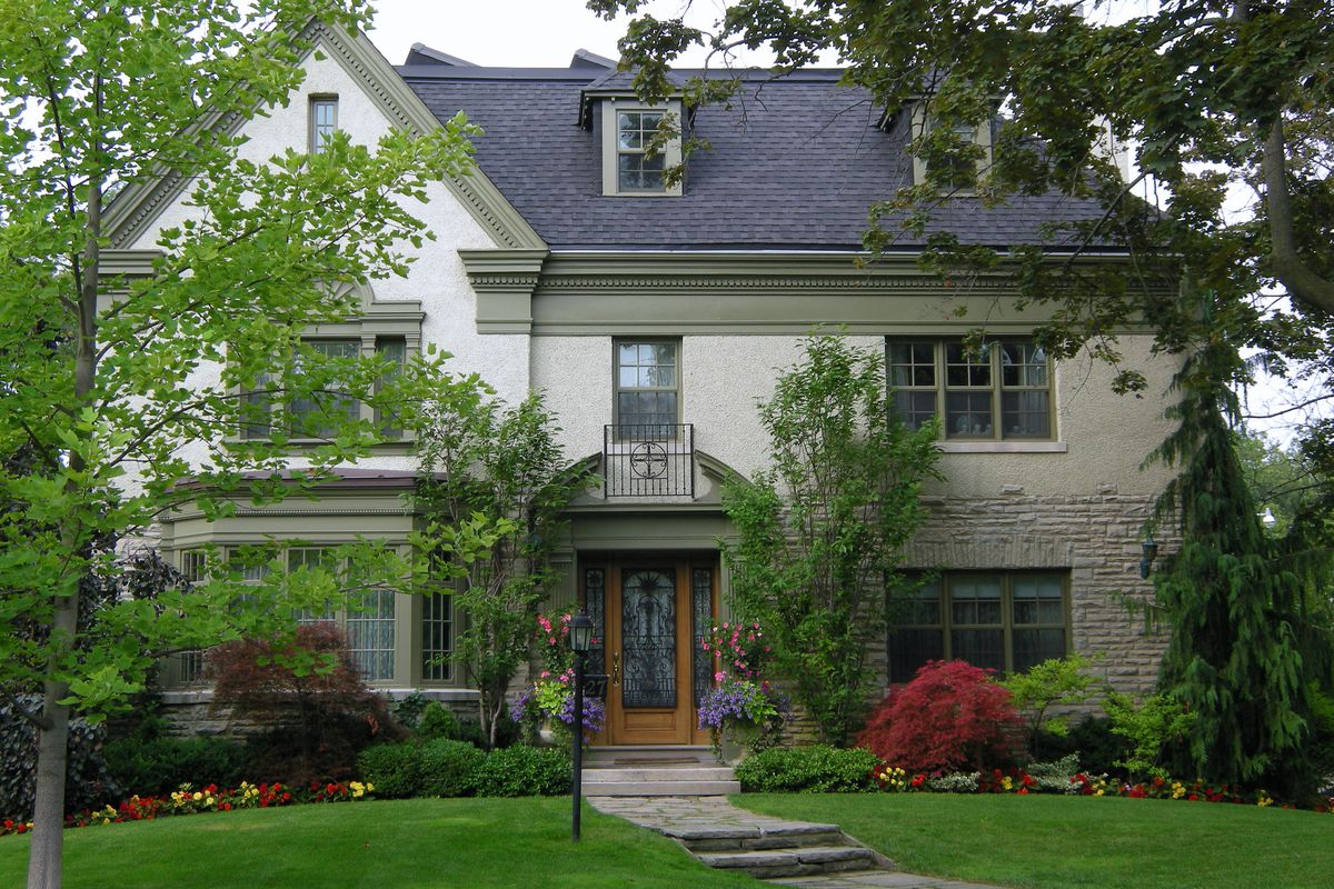 Large suburban home with white paint, stone detailing, large green yard, and flowerbeds.
