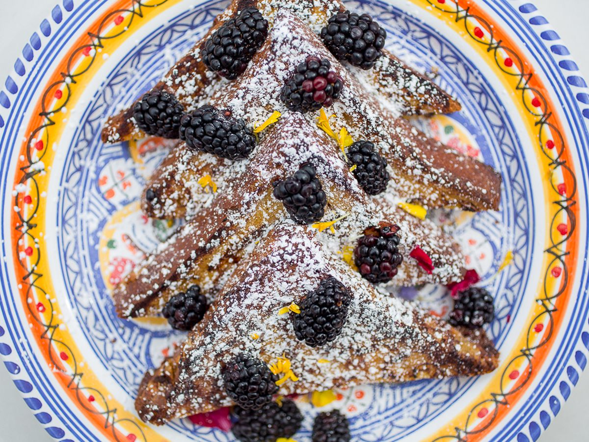 A blue plate with orange and red trim filled with French toast topped with blackberries and powdered sugar