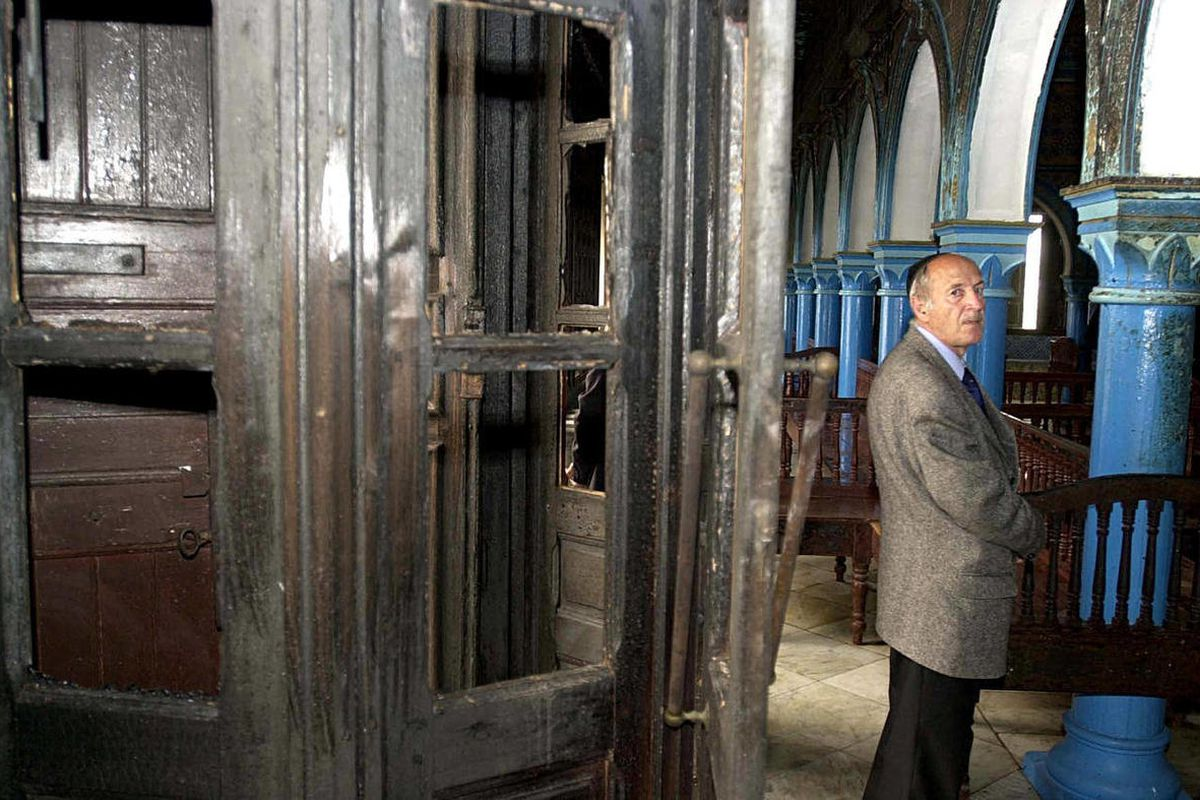 FILE - In this April 12, 2002 file photo, Tunisian consultant for the American Joint Distribution Committee Gilles Maarek examines explosion damage at the Ghriba synagogue, in Houmt Souk, Djerba island, Tunisia. Tunisia's president will be joined Wednesda