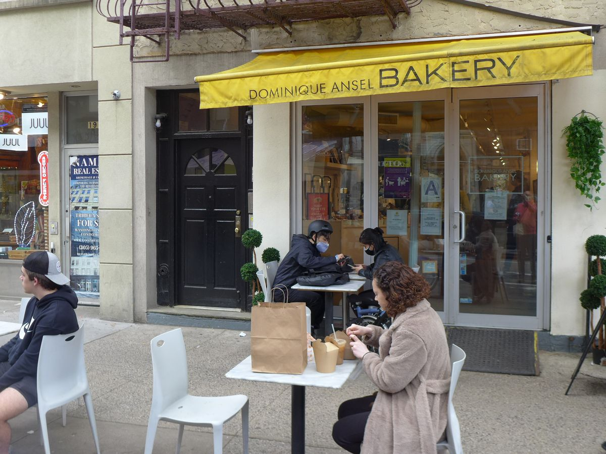 A store with a yellow awning and people sitting at tables in front.