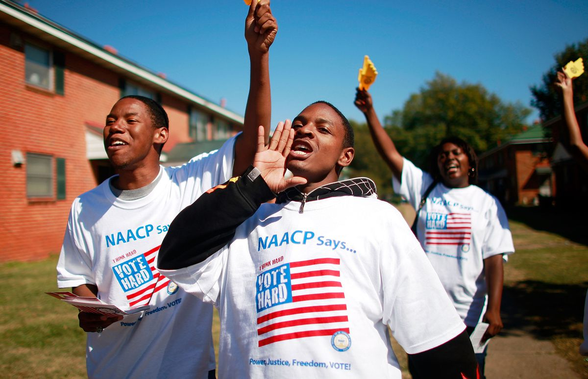 """Three black college students wearing shirts that read, """"NAACP Says ... vote hard,"""" walk and yell through an apartment complex."""