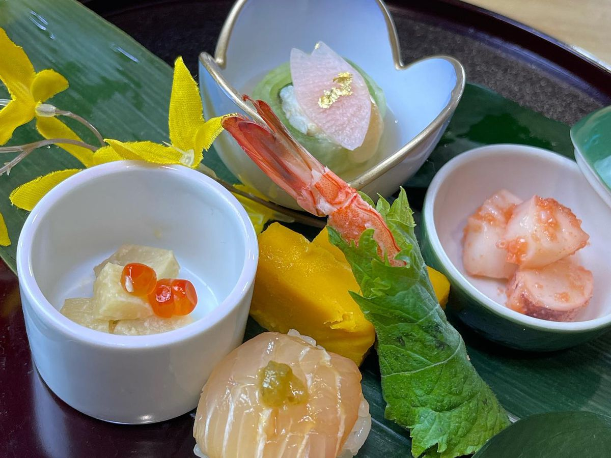 Four small dishes with fish in white bowls