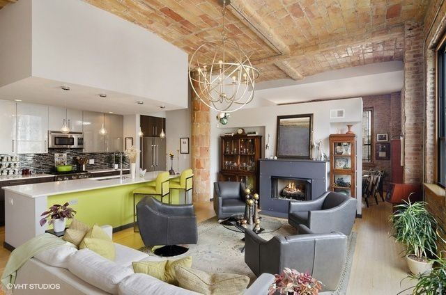 A living area and open kitchen. There are rustic exposed brick details and a pop of yellow-green in the kitchen island.